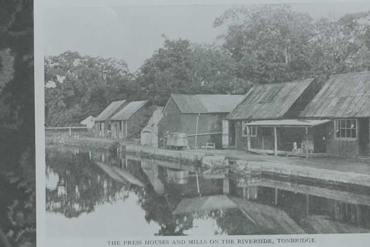 Old photograph of buildings on side of mill stream.