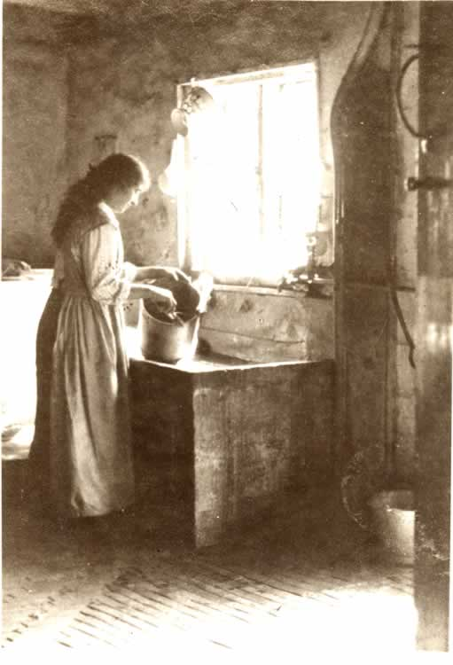 Gladys Axtell washing milk buckets in old kitchen at Great Barnetts.