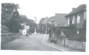 Leigh High Street looking towards Andersons shop and war memorial, so post-1920.  Note no cars; no pavement on left-hand side nor around the Green.