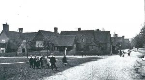 View of Leigh School - note no pavement encircling Green, and children playing on the road.